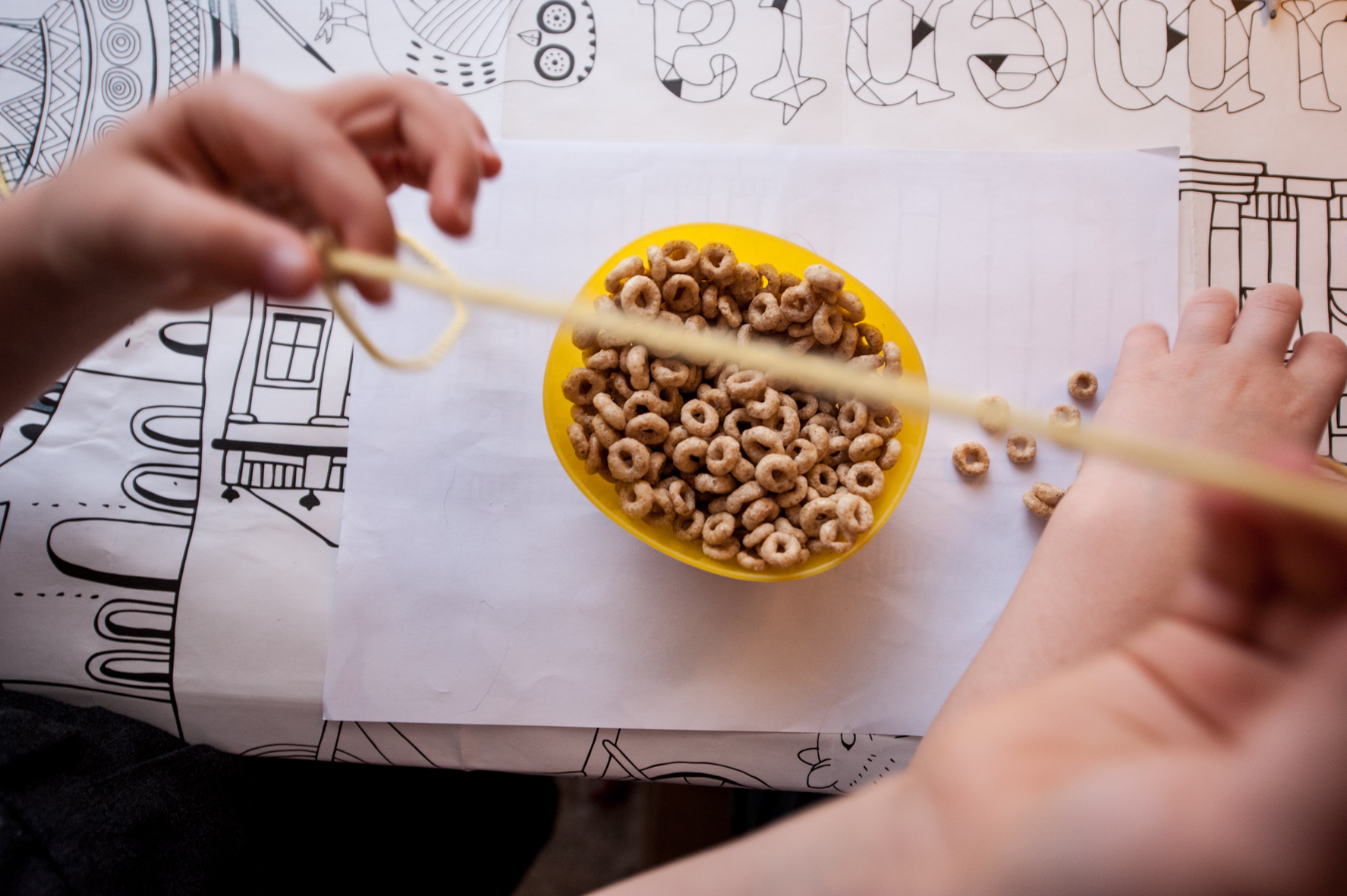 Toddler activities at home - threading cheerios