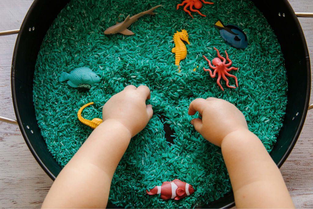 A baby/toddler enjoying a sensory bin with fish figurines and rice inside!