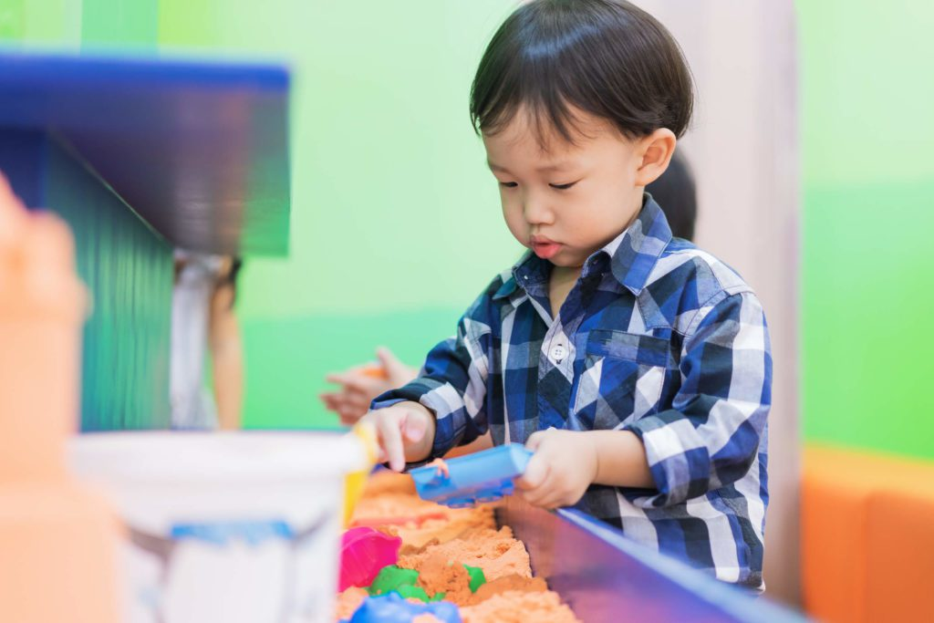 A small toddler playing with in a sand sensory bin