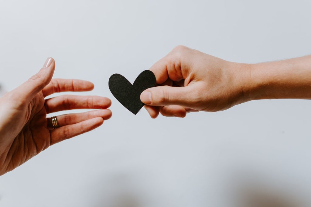 Two hands: one offering a little heart (a little bit of love) to the other.