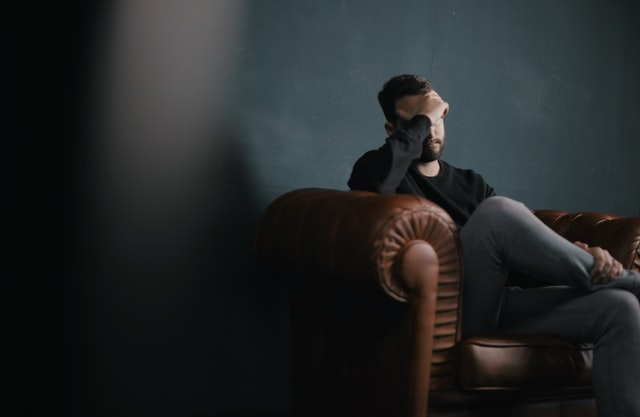 Man sitting on sofa looking low and suffering from their mental health
