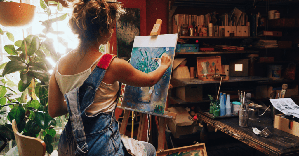 Young woman painting in her art studio to improve her mood