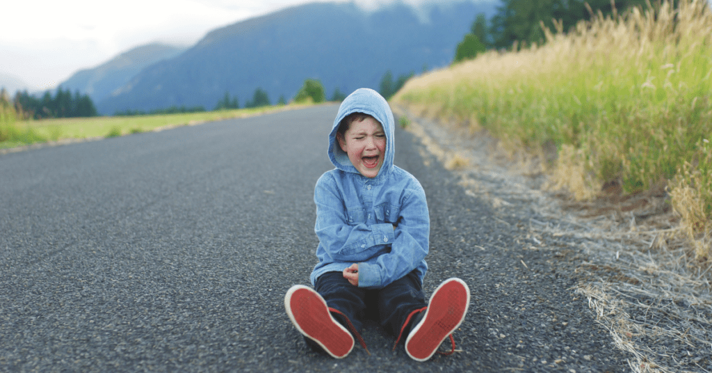 Child is sitting in the middle of a road experiencing a tantrum.